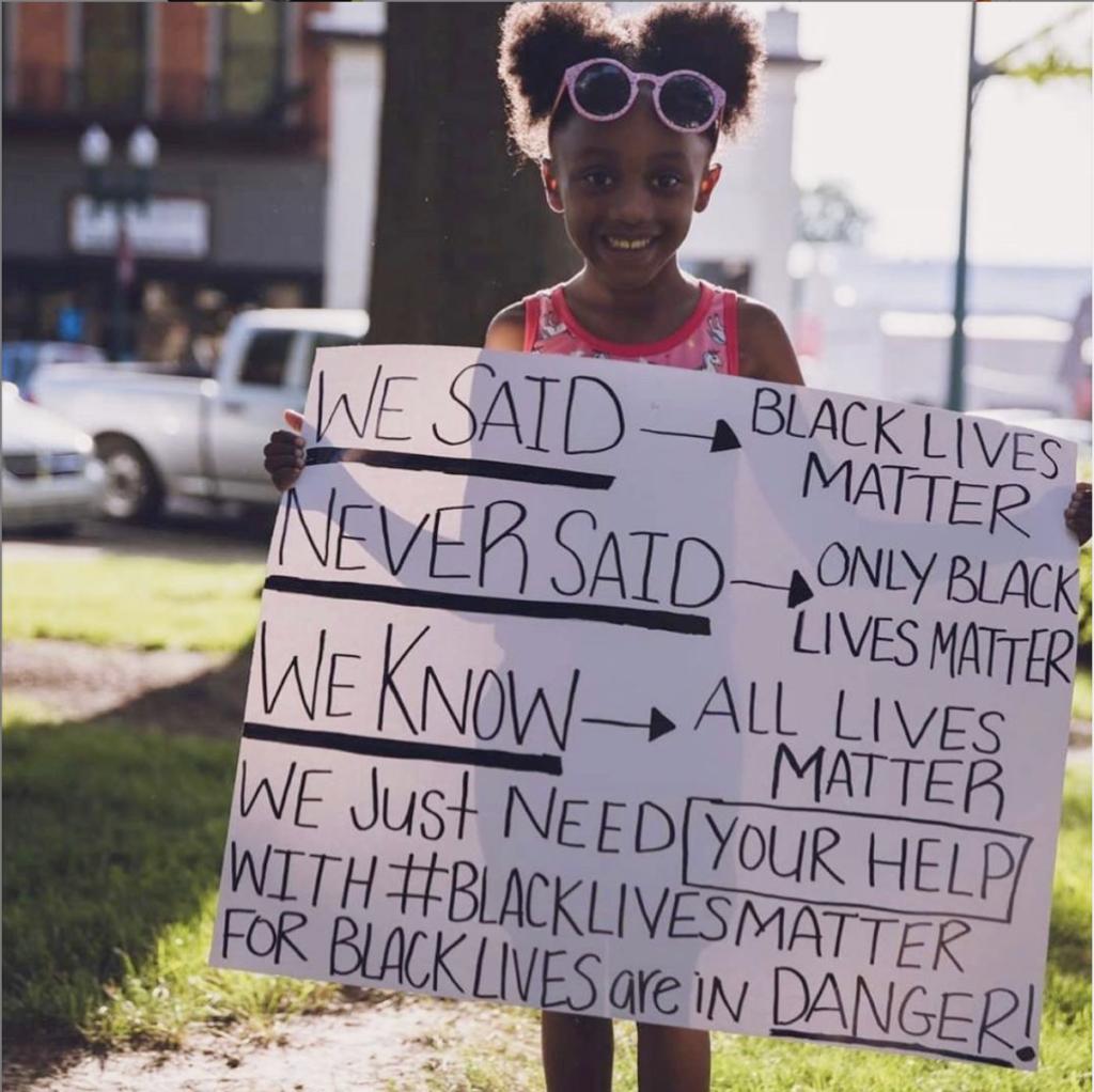 Girl holding sign explaining what black lives matter means